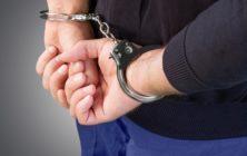 Handcuffs. Arrested man hands close up